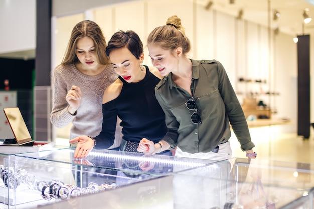 Три девушки смотрят на витрину за покупками в торговом центре