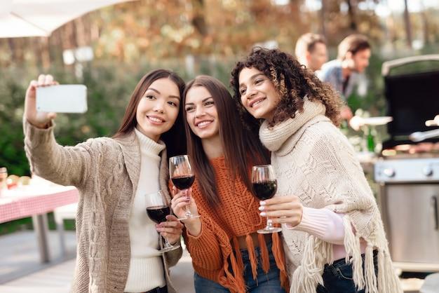 Три девушки делают селфи во время пикника с друзьями.