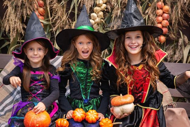 魔女の衣装を着た3人の女の子の姉妹はハロウィーンを祝うのを楽しんでいます