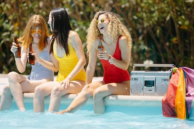 Три девушки сидят и смеются в бассейне, пьют пиво с кассетой и флагом лгбт