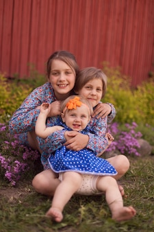 Three girls   sitting near   wooden wall in  spring.happy family concept