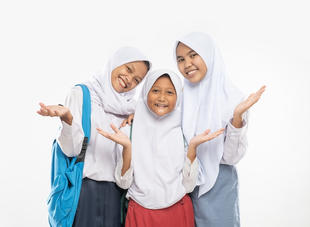 Three girls in veils wearing school uniforms stand with hands gesture offering something while carry...