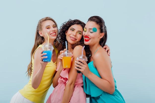 Three girls with artsy make up holding plastic glasses