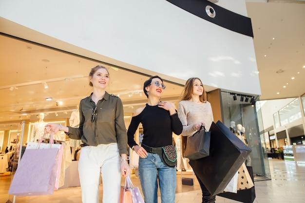 쇼핑 paperbags 걷는 세 매력적인 여자 친구