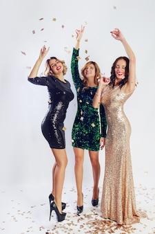 고급 반짝이 장식 조각으로 된 세 명의 매력적인 여성이 춤을 추고 즐겁게 지냅니다. 할리우드 메이크업, 물결 모양의 헤어 스타일. 흰 바탕. 전체 높이.
