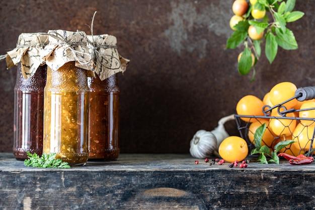 Tre bottiglie di vetro di salsa tkemali georgiana assortita con ingredienti sul tavolo in legno rustico.