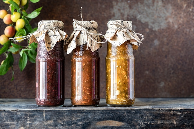 Three glass bottles of assorted georgian tkemali sauce with ingredients on rustic wooden table.