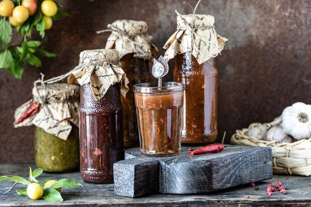 Три стеклянные бутылки ассорти грузинского соуса ткемали с ингредиентами на деревенском деревянном столе.