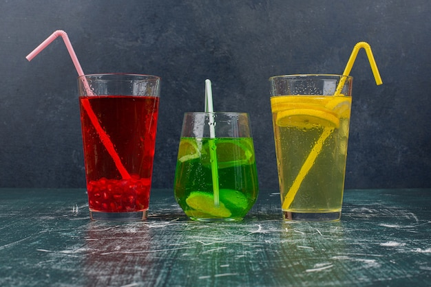 Three glass of coctails with straws on marble table