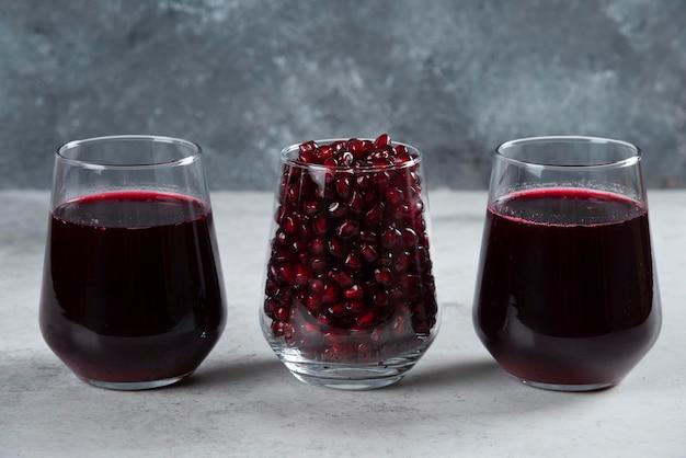 대리석에 석류 주스의 세 유리 컵.