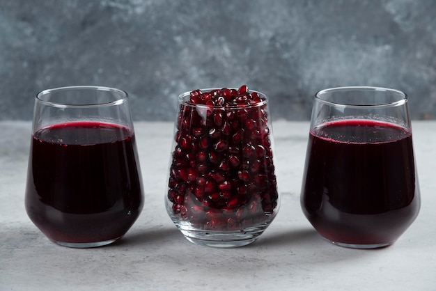 Three glass cups of pomegranate juice on marble.