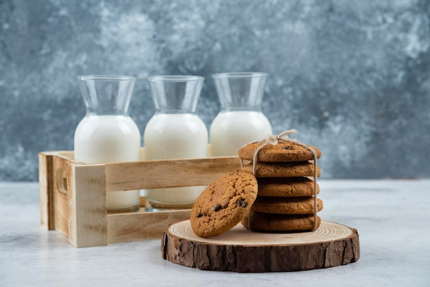 Three glass jar of milk and stack of cookies on marble table.