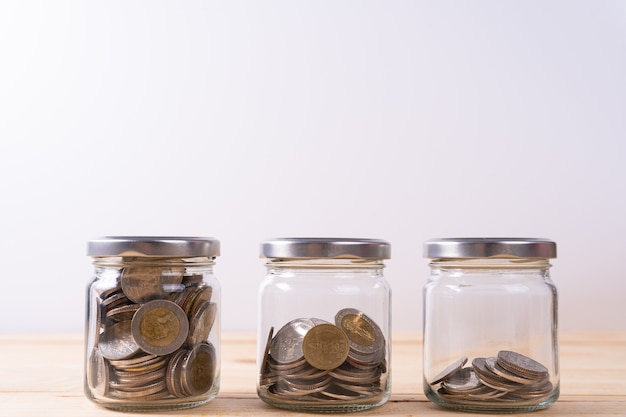 Three glass jars with coins inside on wooden table and white wall