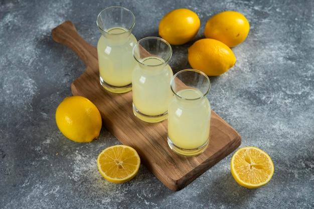 Three glass jugs of cold lemonade on wooden board