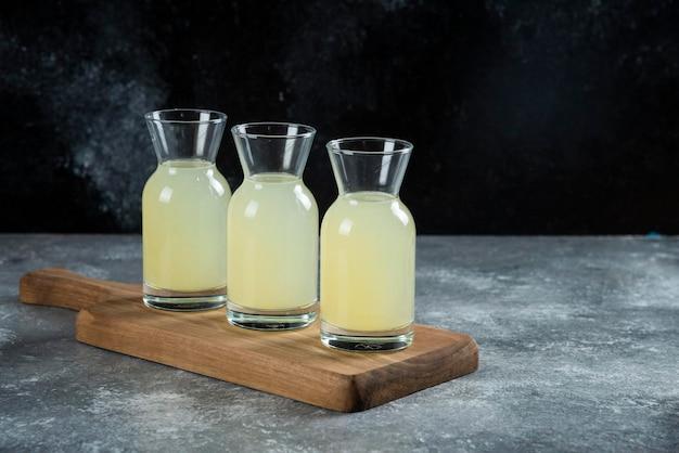 Three glass jugs of fresh lemon juice on wooden board