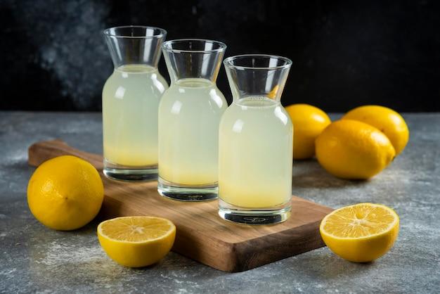 Three glass jugs of tasty lemonade on wooden board