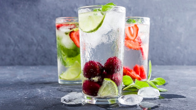Three glass of refreshing cool detox drink with strawberry, lime, cherry and mint on blue background.