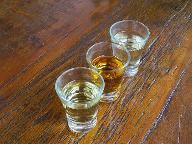 Three glasses of cachaca on wooden table