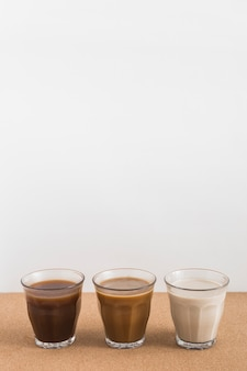 Three glasses displaying different mixtures of milk and coffee on table