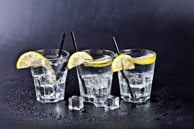 Three glasses of fresh cold carbonated water with ice cubes and lemon slices