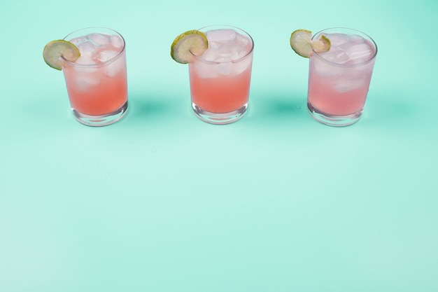 Three glasses of grapefruit juice with lemon slices and ice cubes over the mint background