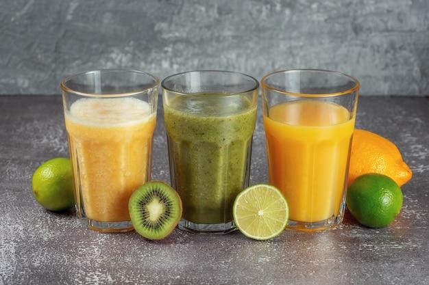 Три бокала подряд с апельсиновым соком и бананом, апельсином, киви и смузи из шпината в окружении половинок фруктов на сером бетонном фоне. понятие о похудании и правильном питании.