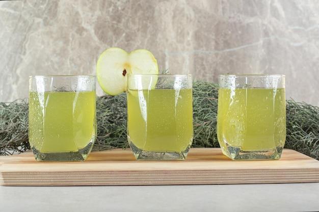 Tre bicchieri di succo di frutta con fetta di mela su tavola di legno