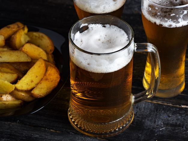 Three glasses of light beer and country potatoes on a dark table