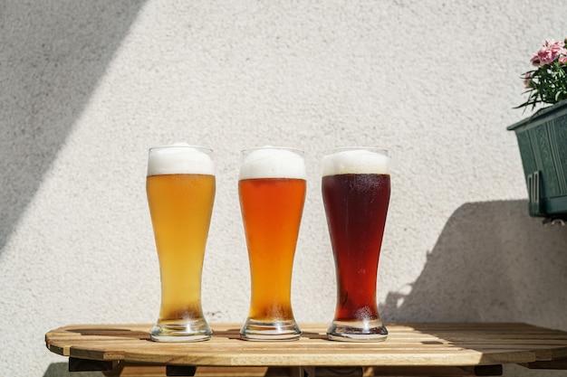 Три стакана пива на деревянном столе на открытом воздухе