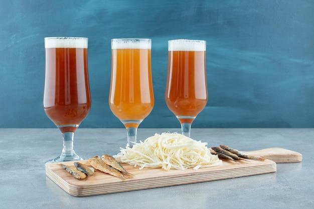 나무 커팅 보드에 생선과 치즈를 넣은 맥주 세 잔. 고품질 사진