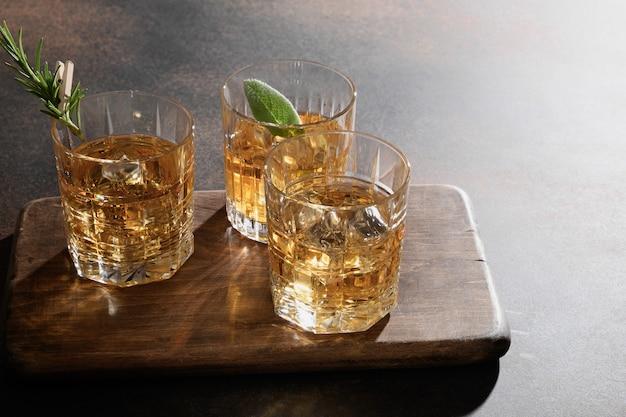 차가운 위스키 세 잔은 로즈마리와 함께 바위에, 레몬 껍질은 브라운에 제공됩니다. 공간을 복사하십시오.