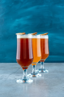 Три стакана светлого пива с рыбой на сером фоне. фото высокого качества