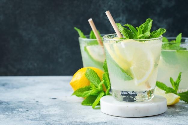 Три бокала коктейля мохито на белом мраморном подиуме и темном размытом фоне