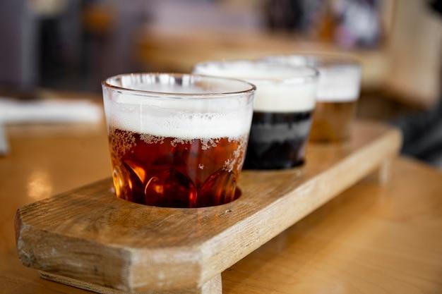 ソフトフォーカスのバーの写真のテーブルにビールの種類が異なる3つのグラス