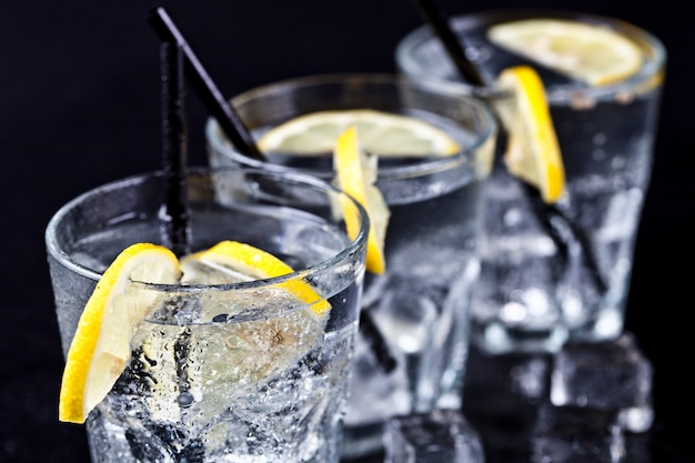 Three glasses with fresh cold carbonated water with lemon slices and ice cubes