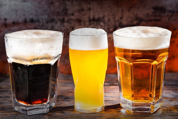 暗い木製の机の上に、新たに注がれた、ろ過されていない、暗いビールが入ったグラス3杯。食品および飲料の概念