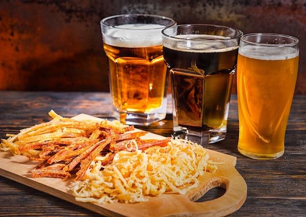가볍고 여과되지 않은 어두운 맥주가 든 세 잔은 어두운 책상에 간식과 함께 나무 도마 근처에 줄 지어 서 있습니다. 음식과 음료 개념