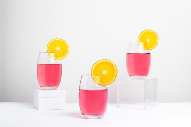 Три бокала с розовой леди коктейль фотогарафадо на белом фоне