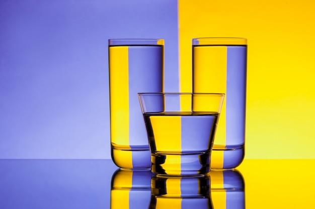 紫と黄色の背景の上の水で3つのグラス。