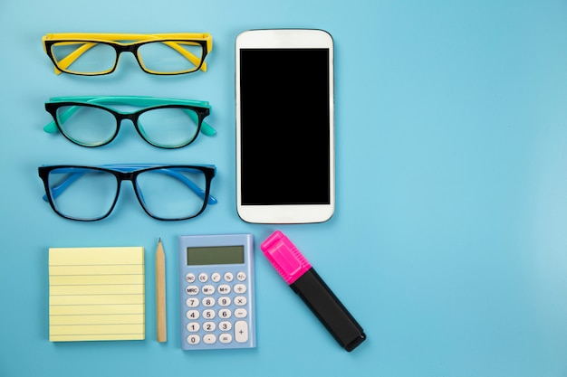 Three glasses yellow notebook mobile phone calculator and hilight marker on blue background pastel style with copyspace flatlay clipping path on screen moblie