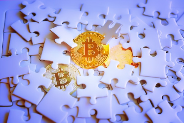 Three gold bitcoin on white jigsaw or puzzle
