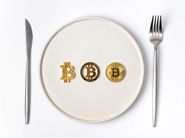 Три золотые монеты биткойн на белой пустой тарелке