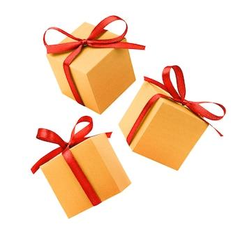 Три золотые подарочные коробки с красным бантом на изолированном белом фоне