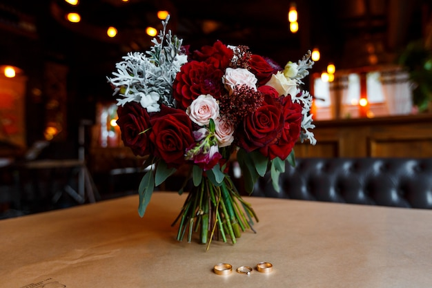 Three gold wedding rings with gemstone and bridal bouquet of red flowers lying on the table