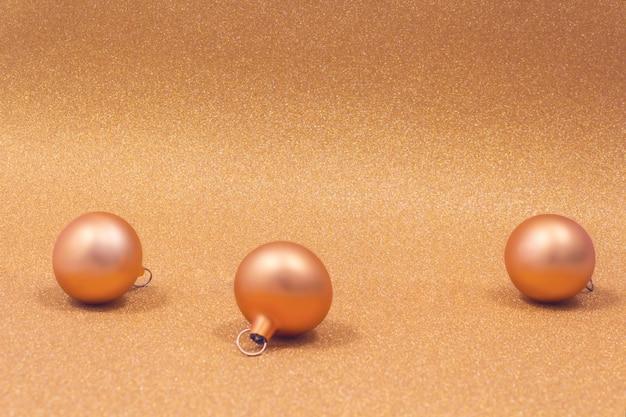 Three golden christmas balls on sparkling .