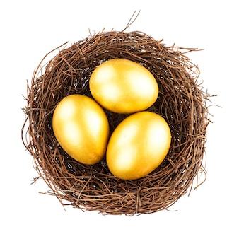 Три золотых яйца в гнезде, изолированные на белом фоне