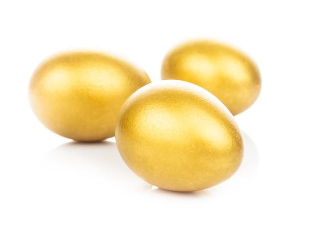 Три золотых яйца, изолированные на белом фоне