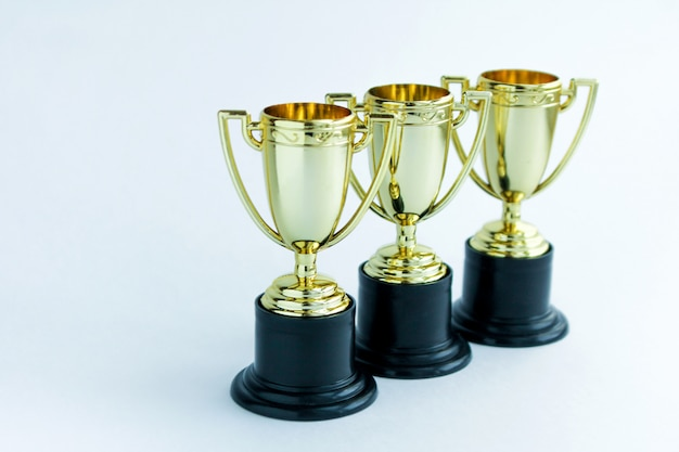Three golden winner cups on a white background. competitions concept.