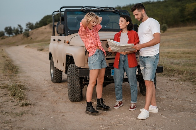 Three good friends checking map while traveling by car