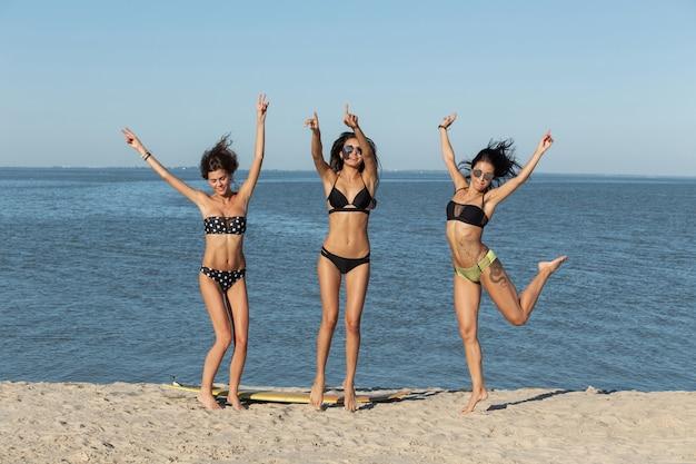 화창한 날, 수영복 차림으로 잘 생긴 검은 머리 소녀 3 명이 바다 근처의 모래 사장에서 서핑 보드 근처에서 점프합니다. .